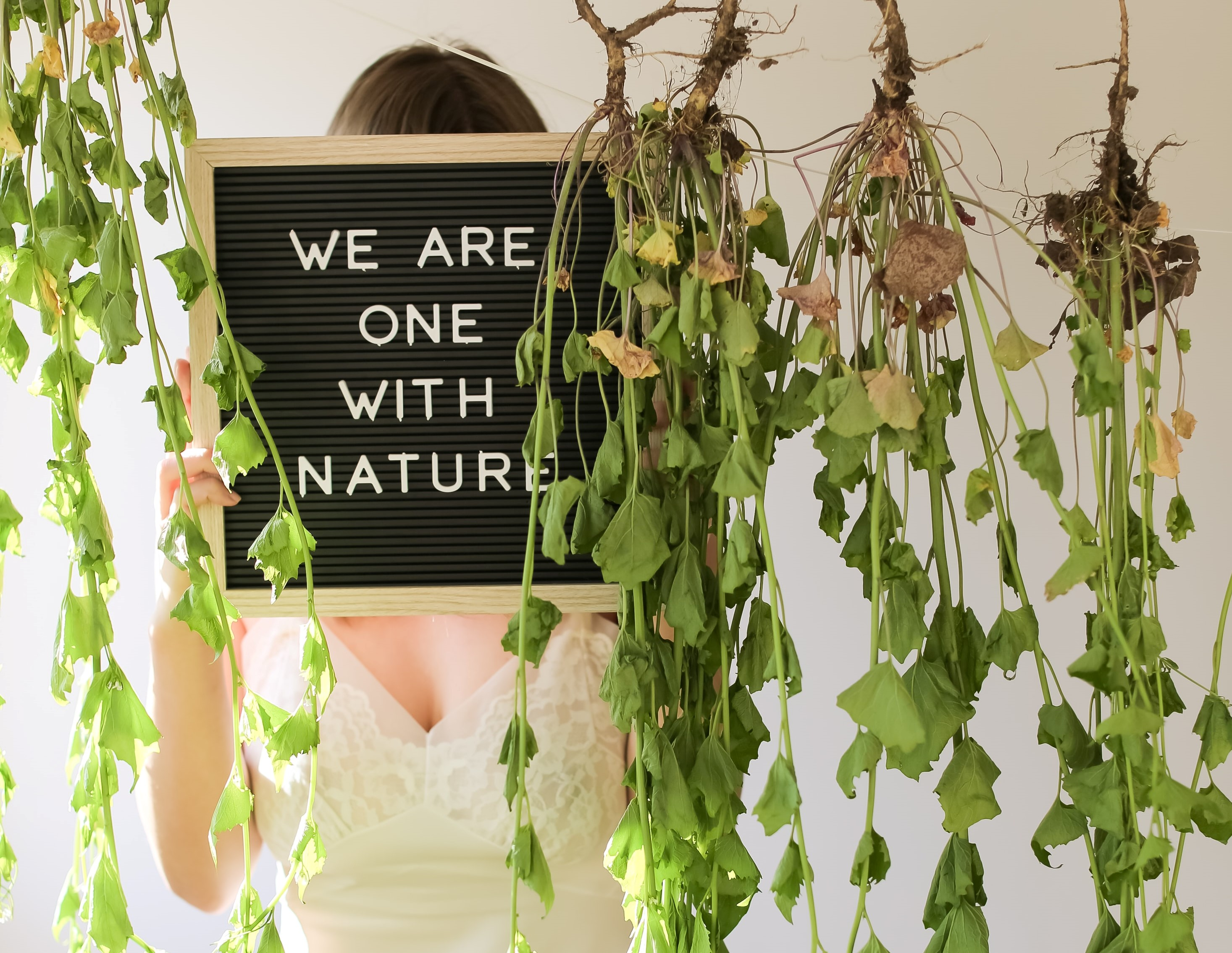 girl holding sign behind hanging green plants